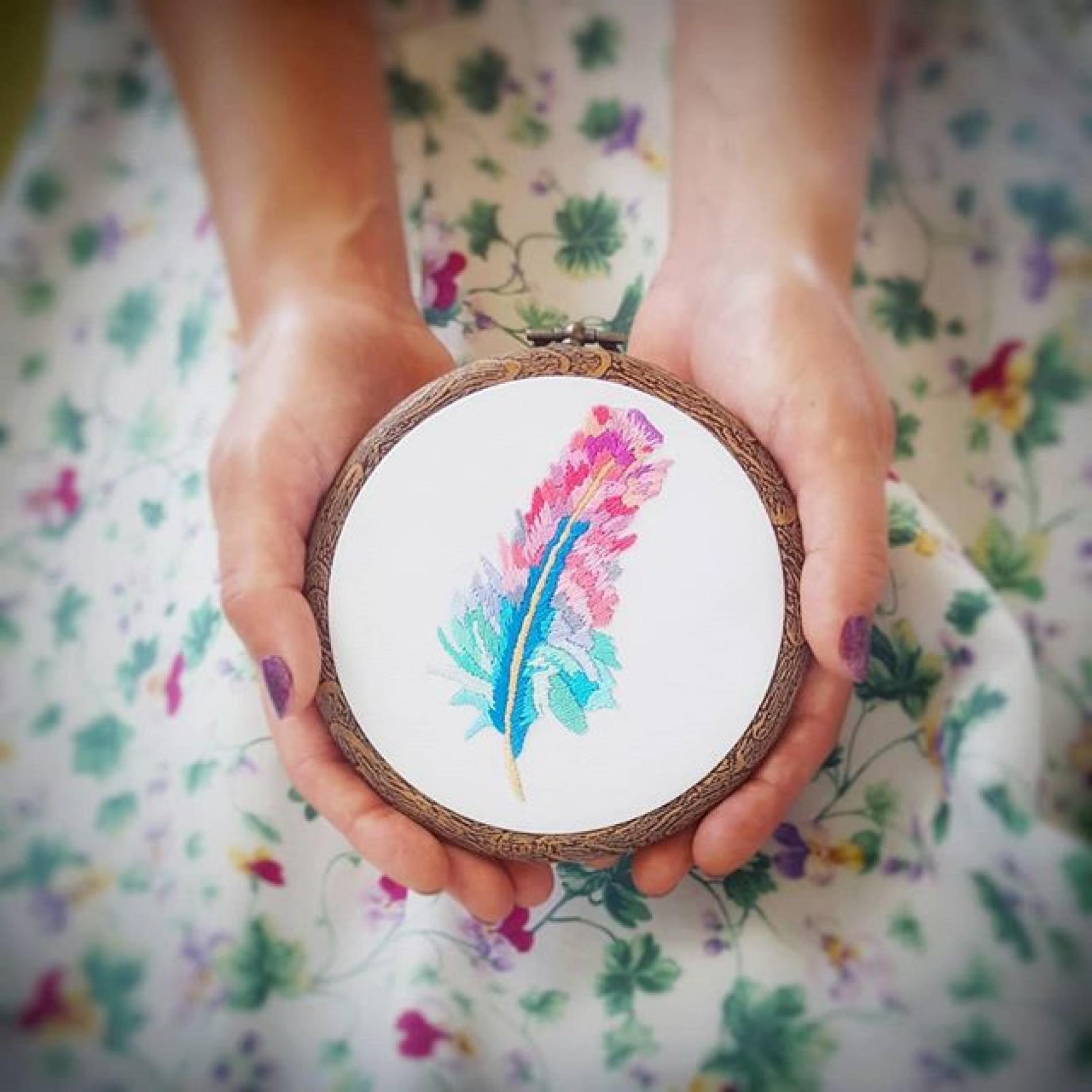 haftowany obraz z różowym piórem